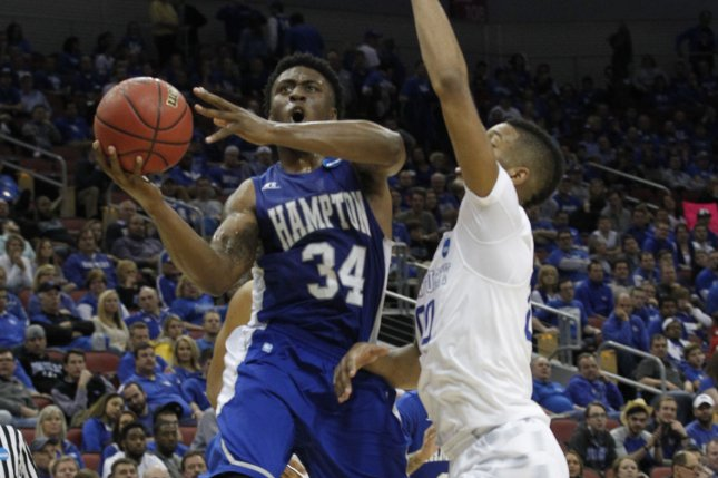 Hampton Pirates' Reginald Johnson (34) fights to get his shot off under pressure from Kentucky Wildcats' Marcus Lee (00) during the second half of play in their second round game of the 2015 NCAA Division I Men's Basketball Championship at the KFC Yum! Center in Louisville, Kentucky, March 19, 2015. Photo by John Sommers II/UPI