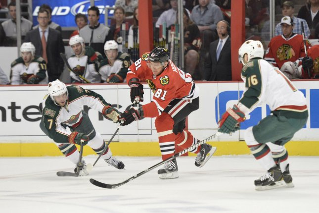 Chicago Blackhawks' Marian Hossa (C) passes the puck as Minnesota Wild's Matt Cullen (L) and Jason Zucker defend during the first period of game 1 of the NHL Western Conference Quarterfinals during the 2013 Stanley Cup Playoffs at the United Center in Chicago on April 30, 2013. File photo by Brian Kersey/UPI