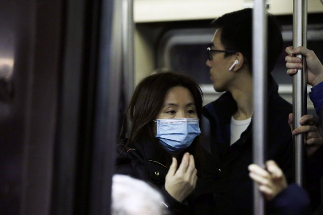 A woman wears a mask covering her mouth and nose while riding the subway on Monday in New York City. Photo by John Angelillo/UPI