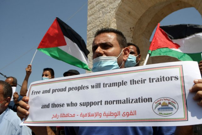 Palestinians carry placards during a protest in Rafah in the southern Gaza Strip, on Saturday to condemn the normalization of ties between Israel, UAE, and Bahrain in a deal announced in Washington by President Donald Trump. Photo by Ismael Mohamad/UPI
