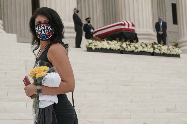 A woman wears a face mask that reads, Nasty and Ready to Vote, after paying tribute Thursday to late Justice Ruth Bader Ginsburg at the U.S. Supreme Court. Nasty is a reference to a famous remark made by Donald Trump during a presidential debate with Hillary Clinton in 2016. Photo by Jemal Countess/UPI