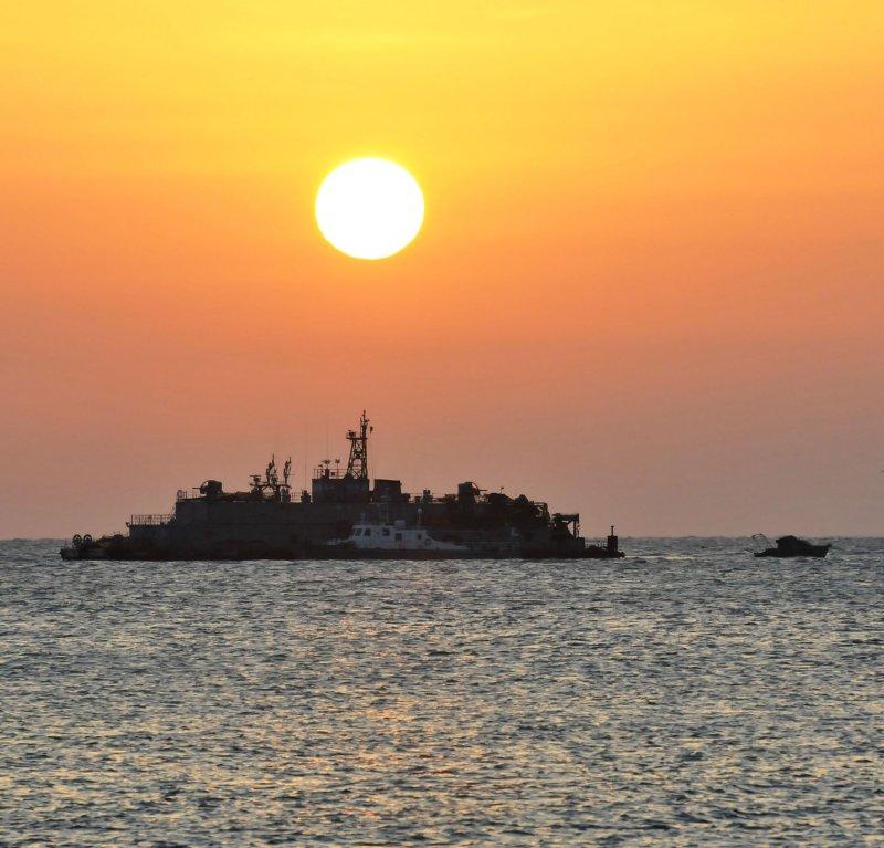 A Korea Coast Guard's ship sails past the South Korean Navy's floating base as the sun rises near Yeonpyeong island, South Korea, on December 23, 2010. UPI/Keizo Mori