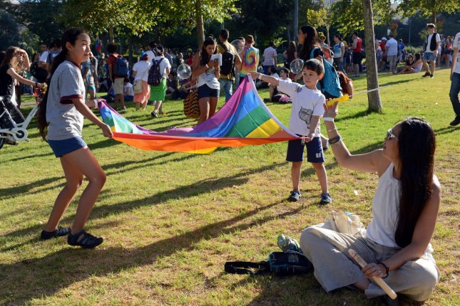 Children play with a rainbow flag at a gathering before the annual Gay Pride Parade in Jerusalem. UPI/Debbie Hill