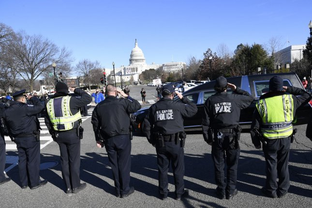 Capitol Hill police salute the passing of the funeral hearse for slain Officer Brian Sicknick, who died in the rioting at the Capitol on Wednesday. Photo by Mike Theiler/UPI