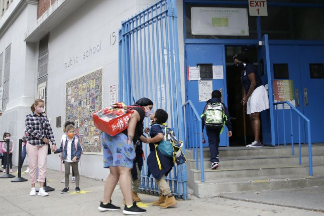 Parents and children are seen at Public School 15 in New York City on September 29, 2020. More than 1 million students are scheduled to return to classrooms on Monday. File Photo by John Angelillo/UPI