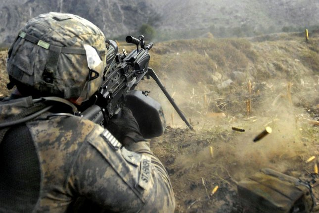 Army Pvt. John Stafinski, an infantryman with 3rd Platoon, Company C, 2nd Battalion, 12th Infantry Regiment, fires his squad automatic weapon into an anti-Afghan forces location during a firefight in the Waterpur Valley, in Afghanistan's Kunar Province, November 3, 2009. UPI/Cody A. Thompson/U.S. Army.