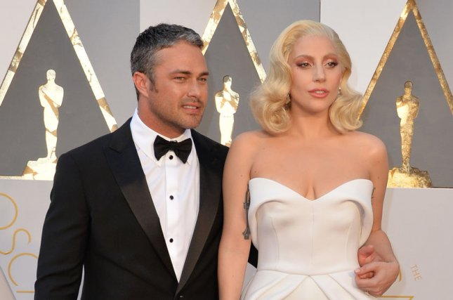Lady Gaga (R) and Taylor Kinney at the Academy Awards on February 28. File Photo by Kevin Dietsch/UPI