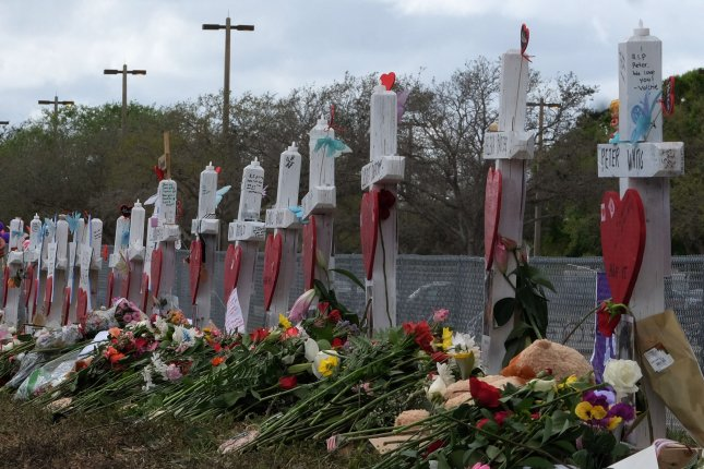 Flowers are stacked Monday by markers representing students and teachers killed last week at Marjory Stoneman Douglas High School in Parkland, Fla. Photo by Gary Rothstein/UPI