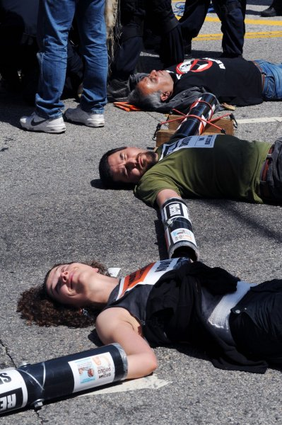 Protesters lie on a street with their hands linked together during a demonstration organized by We Are All Arizona against Arizona's new law SB1070, near the U.S. Immigration and Customs Enforcement offices in downtown Los Angeles May 6, 2010. The law requires state and local police to determine people's immigration status if there is reasonable suspicion they are in the United States illegally. UPI/Jim Ruymen