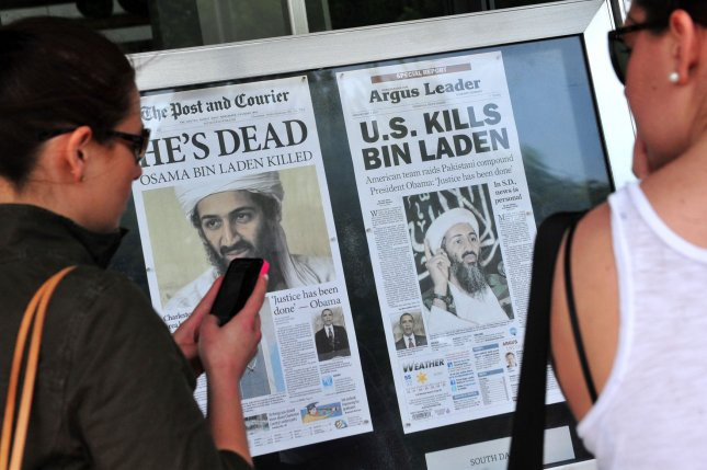 People stop to look at the front page headlines from around the country that announce the death of Al-Qaida terror leader Osama bin Laden in front of the Newseum in Washington on May 2, 2011. UPI/Kevin Dietsch