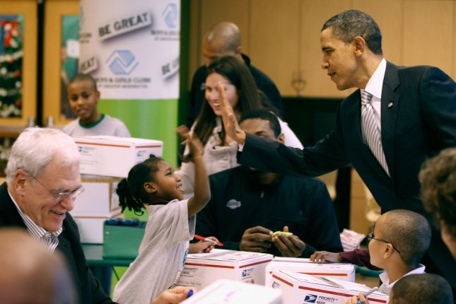 U.S. President Barack Obama (R) gives a girl a high-five while helping Los Angeles Lakers head coach Phil Jackson (L) and other team members and children volunteers fill care packages during a NBA Cares service event at the Boys and Girls Club in Washington D.C. UPI/Chip Somodevilla/Pool