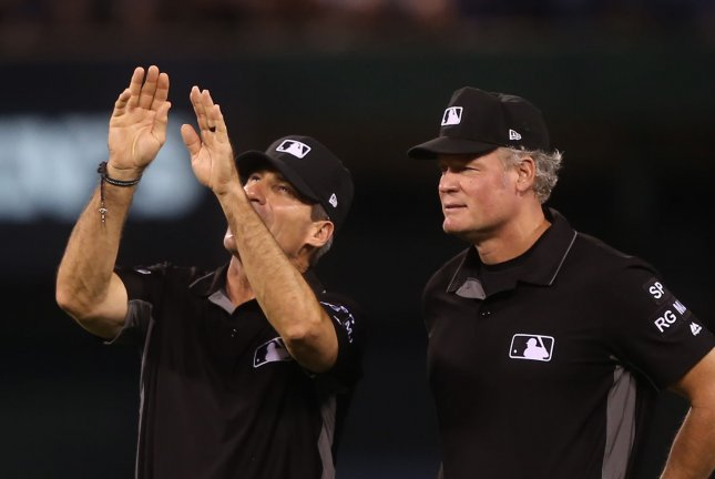 MLB umpire Angel Hernandez (L) explains a point to Ted Barrett between innings of the Atlanta Braves-St. Louis Cardinals at Busch Stadium in St. Louis on August 12, 2017. File photo by Bill Greenblatt/UPI