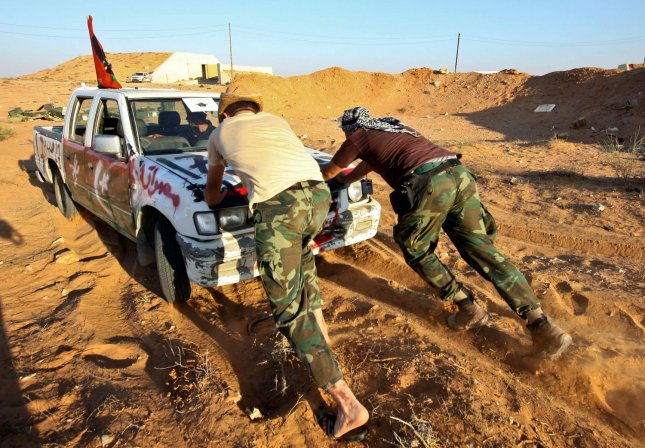 Libyan fighters loyal to the new regime, push a car in the desert before heading to the frontline in the nearby city of Sirte in eastern Libya, on September 23, 2011 , one of the last hold-outs of the the ousted dictator Moamer Kadhafi's forces. Desperate residents fled Moammar Kadhafi's hometown Sirte on Friday, as fighters of Libya's interim government probed the city's eastern outskirts in anticipation of a final assault on one of the fallen leader's two remaining bastions. UPI/ Amru Taha