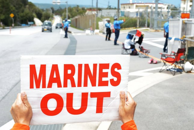 An activist holds a sign in front of the U.S. Marine Corps' Camp Schwab in Nago, Okinawa, Japan, on June 17, calling for the removal of American servicemembers from the installation and others on the Japanese island. Friday, a Japanese court ruled in favor of a project to relocate the Marine Corps' nearby Futenma Air Station to a location near Camp Schwab, in Oura Bay in Henoko. The controversial project has been debated in Okinawa and Tokyo for 20 years. File Photo by Keizo Mori/UPI