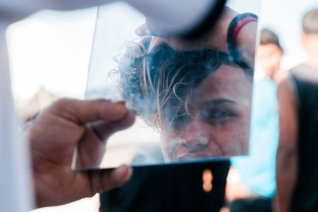 Jose Hernández, 17, styles his hair at El Barretal shelter in Tijuana, Mexico, on Sunday. Hernández traveled without his family from Honduras in hopes of seeking asylum in the United States. Photo by Ariana Drehsler/UPI