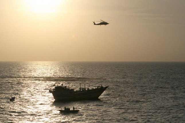 A U.S. military helicopter and an Iranian fishing vessel are seen in the Arabian Sea. An oil tanker belonging to a London-based company was attacked in the sea on Thursday, officials said. File Photo by U.S. Navy/UPI