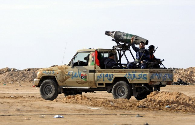 A Libyan rebel flashes the V-sign for victory as sit on to an armed vehicle at the western gate of the strategic restive town of Ajdabiya, on April 20, 2011. France and Italy joined Britain in sending military advisers to insurgent-held eastern Libya, as Tripoli warned that foreign boots on the ground would prolong the conflict. UPI\Tarek Alhuony.
