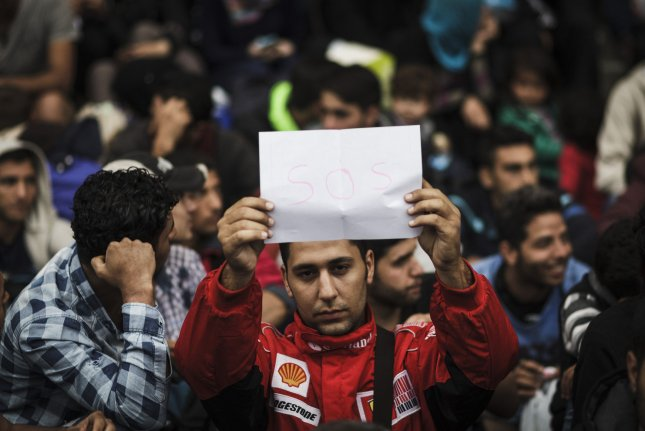 A refugee from Syria holds a sign asking for help during a sitting protest outside the Keleti train station in Budapest, where 200 Syrian refugees gathered in an effort to pressure the Hungarian government to provide them with trains or buses to transport them to the Austrian border on September 5, 2015. Photo by Achilleas Zavallis/UPI