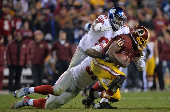 New York Giants defensive tackle Johnathan Hankins (96) and defensive end Justin Tuck (91) sack Washington Redskins quarterback Robert Griffin III in the fourth quarter at FedEx Field in Landover, Maryland. File photo by Kevin Dietsch/UPI