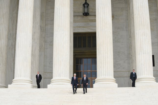 Supreme Court Associate Justice Neil Gorsuch (L) and Chief Justice John Roberts walk down the steps in front of the court in Washington, D.C., on Thursday following the jurist's formal swearing-in ceremony. Gorsuch was sworn-in April 10, but Thursday's ceremony officially and symbolically installed him on the bench. Photo by Pat Benic/UPI