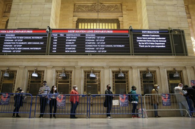 People stand under train schedules near ticket booths as they wait in line to be vaccinated at a pop-up vaccine site in Vanderbilt Hall at Grand Central Terminal on Wednesday. Photo by John Angelillo/UPI