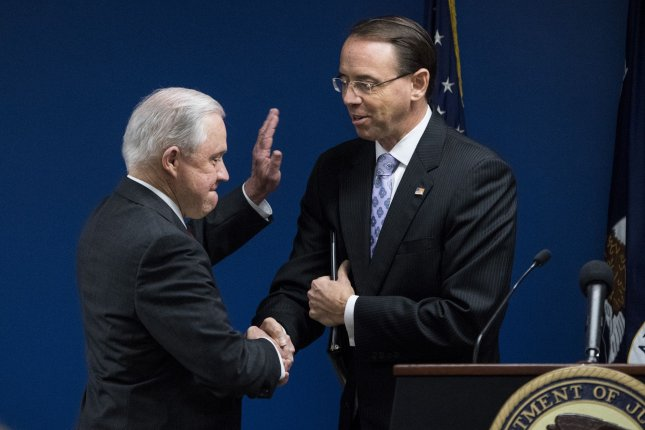 Attorney General Jeff Sessions shakes hands with Deputy Attorney General Rod Rosenstein as he takes the podium to speak on transnational crime at the U.S. Attorney's Office in Washington, D.C., Monday. Photo by Kevin Dietsch/UPI