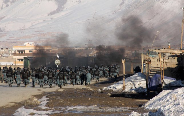 Afghan policemen walk past burning tires during an anti-U.S. demonstration in Kabul, Afghanistan, on Friday, February 24, 2012. Thousands of Afghans staged new demonstrations Friday over the burning of Korans at a U.S. military base in Afghanistan. UPI
