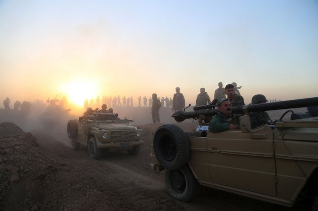 Iraq's military said the 100 decapitated bodies of civilians were found in a mass grave at a school near the town of Hammam al-Alil, which is about 18 miles south of Mosul. In this image, an Iraqi Kurdish Peshmerga convoy moves through positions in Mount Zardak, near east Mosul, as they take part in an operation against the Islamic State on Oct. 17. Photo by Shvan Harki/UPI