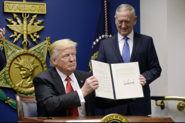U.S. President Donald Trump, with Denfense Secretary James Mattis, holds up one of two executive orders he signed on January 27. One provides new resources and equipment to strengthen the U.S. military. File Pool Photo by Olivier Douliery/UPI