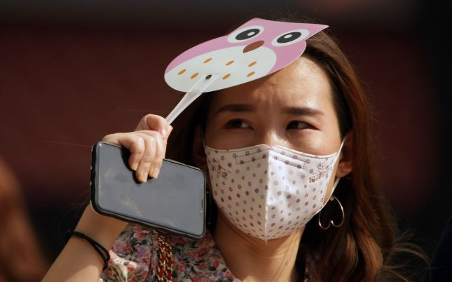 A Chinese woman wears a mandatory protective face mask while shopping at an international fashion mall in Beijing on Sunday,. Despite China's claims to have stopped the threat of COVID-19 re-emerging in the capital, Chinese are encouraged, and in many places ordered, to continue wearing face masks. Photo by Stephen Shaver/UPI