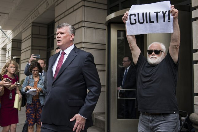 Kevin Downing, attorney for former Trump campaign chairman Paul Manafort, leaves the court house followed by a protester after Manafort plead guilty as part of a plea deal in his fraud trail, outside of the District Court in Washington, D.C. on Friday. Photo by Kevin Dietsch/UPI