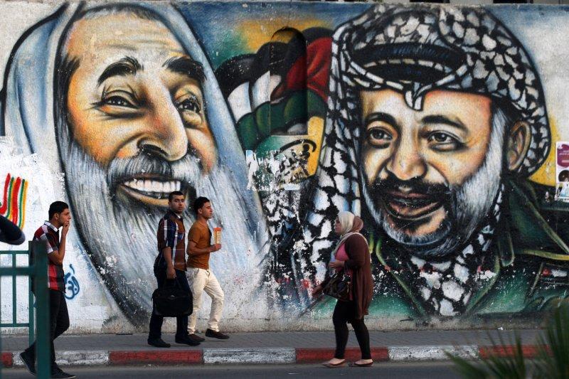 Palestinians students walks past a mural depicting late Palestinian leader Yasser Arafat (R) and late Hamas spiritual leader Ahmed Yassin, in Gaza City November 10, 2013. UPI/Ismael Mohamad