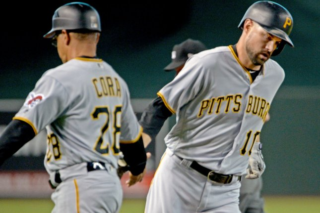 Pittsburgh Pirates' Jordy Mercer shakes hands with third base coach Joey Cora as he heads home after hitting a home run in the fourth inning against the Arizona Diamondbacks on June 13 at Chase Field in Phoenix. Photo by Art Foxall/UPI