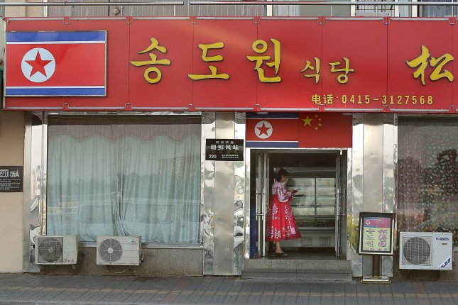A North Korean woman and hostess stands outside a North Korean restaurant waiting for customers in Dandong, China's largest border city with North Korea. Mobile phone use is growing in the country of 25 million. Photo by Stephen Shaver/UPI