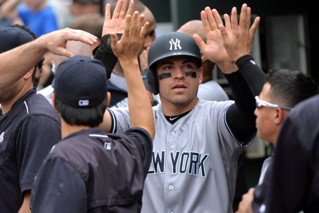 New York Yankees' Jacoby Ellsbury is congratulated in the dugout. Photo by Kevin Dietsch/UPI
