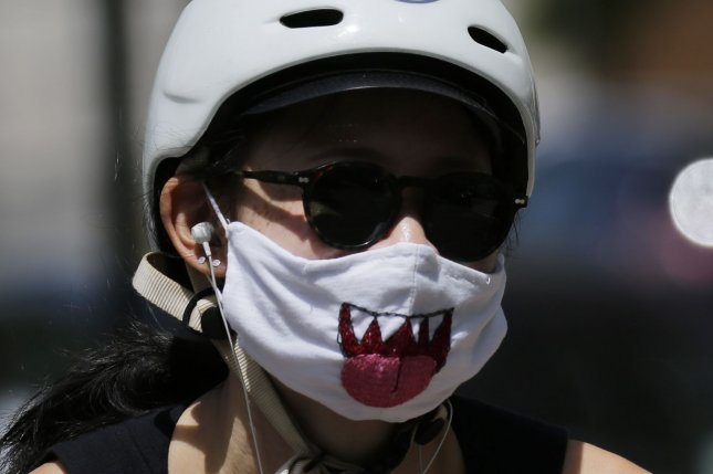 Models are now predicting the United States could see 300,000 deaths from COVID-19 by December. Pictured, a woman wears a protective face mask while riding a bicycle on the Upper West Side of Manhattan in New York City in May. Photo by John Angelillo/UPI