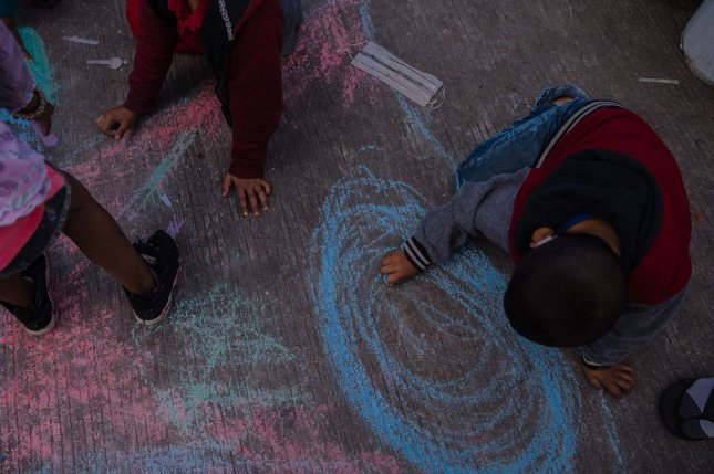 Children draw with chalk on the ground at El Chaparral plaza in Tijuana, Mexico on Friday. Hundreds of asylum seekers have set up tents near the port of entry in hopes of being able to seek asylum in the United States. Photo by Ariana Drehsler/UPI