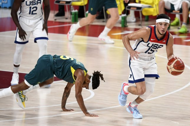 The United States' Devin Booker (R) dribbles away from Australia's Patty Mills during the men's basketball semifinals at the Tokyo 2020 Olympics on Thursday. Photo by Mike Theiler/UPI