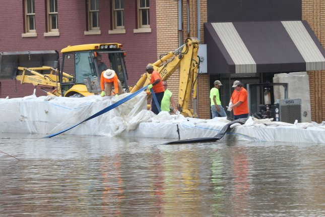 City workers adjust hoses and reinforce plastic on a levee constructed to keep Mississippi River floodwater away from businesses in the downtown area of Alton, Ill., on Friday. Photo by Bill Greenblatt/UPI