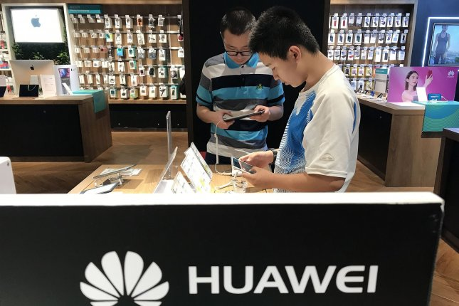 Shoppers look at smartphones on August 14 at a Huawei shop in Beijing, China. Photo by Stephen Shaver/UPI