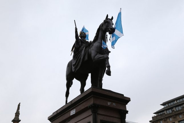 Scottish national flags are posted on a statue in George Square in Glasgow, Scotland. The nation's finance minister has resigned over inappropriate communications with a 16-year-old boy, leader Nicola Sturgeon said Thursday. File Photo by Hugo Philpott/UPI
