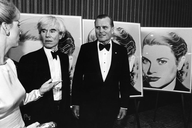Andy Warhol (C) stands in front of a limited edition serigraph of Princess Grace of Monaco on June 1, 1984, in Philadelphia. On June 3, 1968, radical feminist author and actor Valerie Solanas shot Warhol at his New York City studio The Factory. File Photo by George Bilyk/UPI