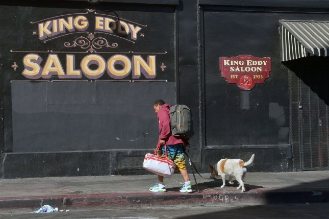 A man and his dog walk past a closed bar in Los Angeles, Calif. Federal officials said Thursday that more than 900,000 U.S. workers have filed new unemployment claims. File Photo by Jim Ruymen/UPI