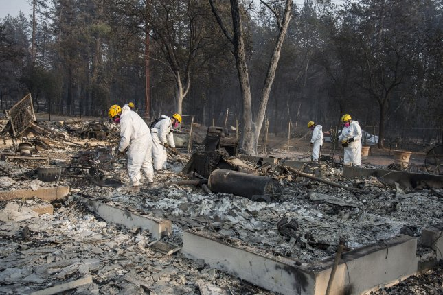 Members of the Mendocino County Sheriff's Department Search and Rescue rake through ruins in Paradise, Calif., on Saturday. Victims of the Camp Fire have filed a class-action lawsuit against Pacific Gas & Electric, accusing the utility of being responsibile for California's most deadly and widspread fire. Photo by Terry Schmitt/UPI