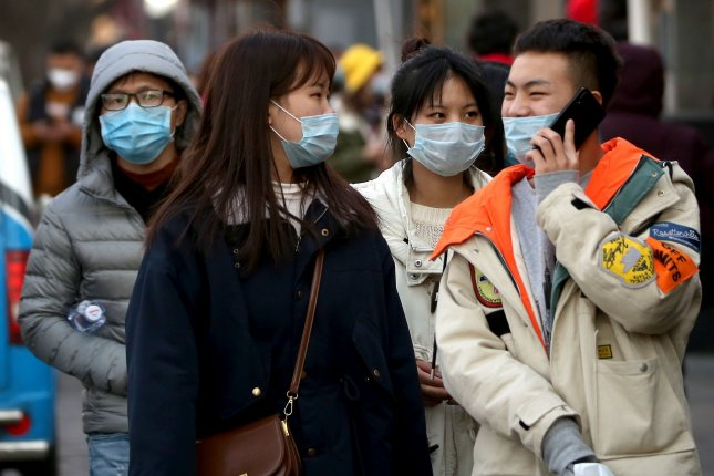 Pedestrians wear protective respiratory masks in Beijing on January 23, 2020, the same day the government issued lockdown orders for the city of Wuhan over a coronavirus outbreak. File Photo by Stephen Shaver/UPI