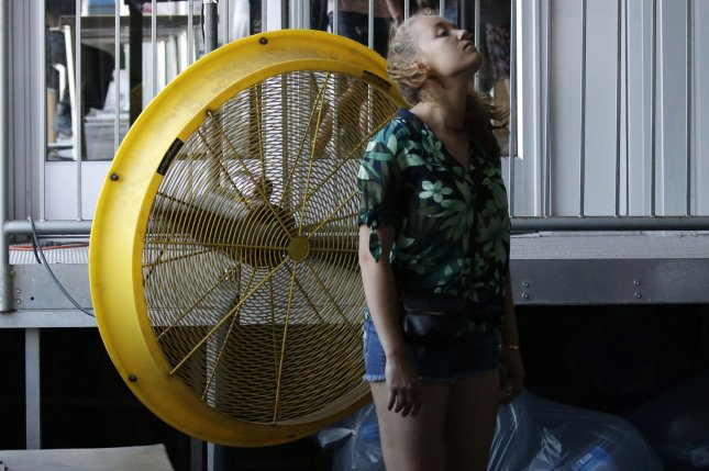 A girl cools off at a fan in 2018 in New York City on the fourth straight day temperatures had topped 90 degrees. Researchers say climate change could cause extreme heat exposure to increase 30-fold by the end of the century. Photo by John Angelillo/UPI