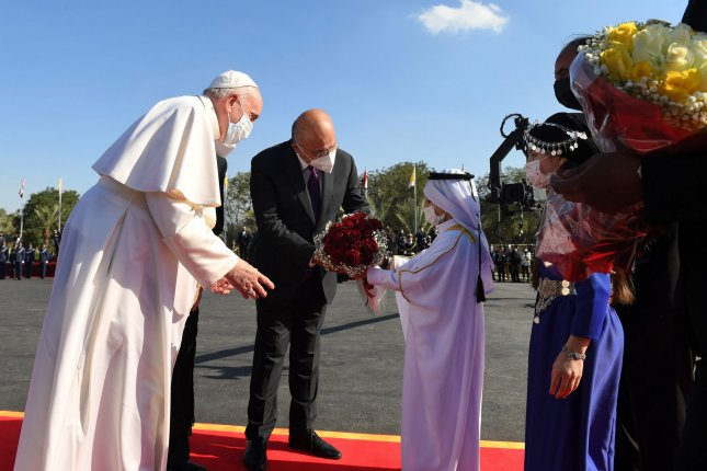Pope Francis (L) receivesa bouquet of flowers from a child upon his arrival at at Baghdad Airport in Iraq on Friday. Photo by Office of the Iraqi President/UPI