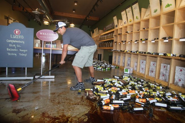 Dewey Lucero, owner of Lucero Olive Oil, cleans up broken bottles of olive oil at his business after a 6.0-magnitude earthquake in Napa, California, on August 24, 2014. UPI/David Yee