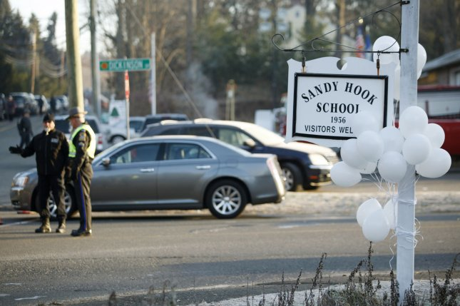 Florida Atlantic University fired a professor who claimed the Sandy Hook Elementary School shooting that left 26 dead was a hoax and publicly argued with a victim's parents. Pictured: A bunch of white balloons cover the school's sign while police officers block the road leading to the school in Connecticut on December 15, 2012. Photo by Matthew Healey/UPI