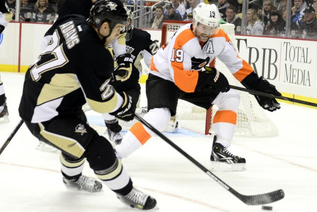 Former Pittsburgh Penguins right wing Craig Adams (27) plays the puck away from Philadelphia Flyers left wing Scott Hartnell (19) at the Consol Energy Center in Pittsburgh on November 13, 2013. UPI/Archie Carpenter